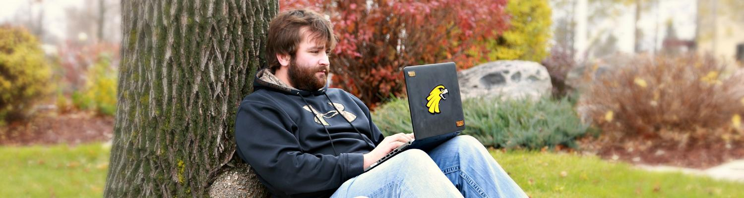 man with laptop against tree