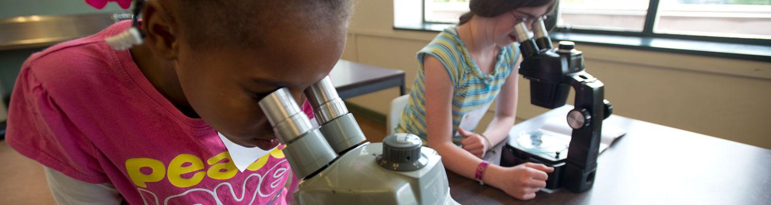 two young girls looking into microscopes